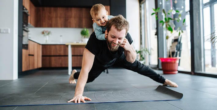 man doing home exercise with baby on back
