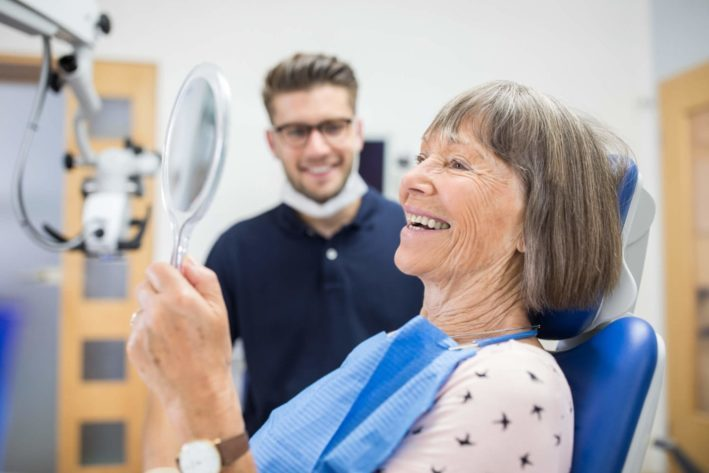 elderly woman smiling into mirror at dentist