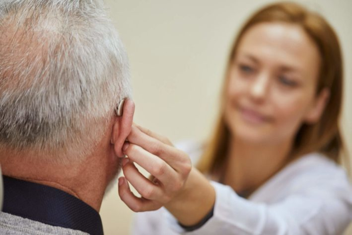 Female doctor attaching hearing aid to elderly man