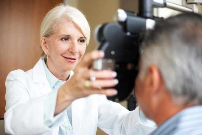 eye doctor performing eye exam on male client