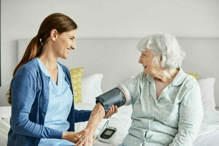 home health care provider helping elderly patient at her home