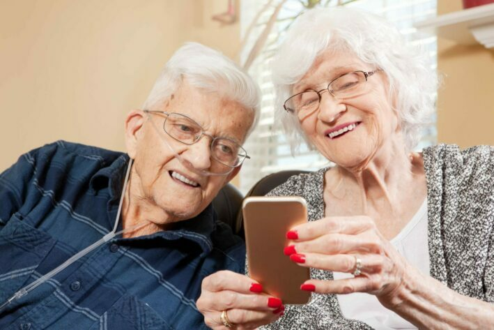 senior man with COPD and woman looking at a phone