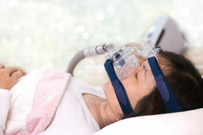 patient in hospital with oxygen mask on treating sleep apnea