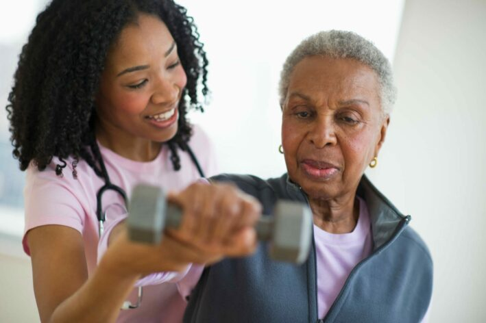 senior patent with female doctor lifting dumbbell during physical therapy